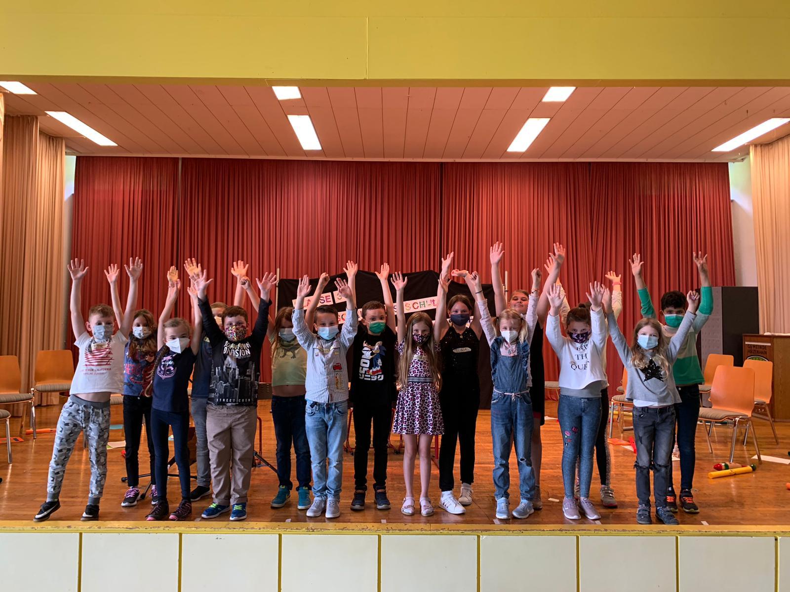 Schülerinnen und Schüler der Klasse 3a der Hugo-Buderus-Schule in Hirzenhain jubelnd auf der Bühne