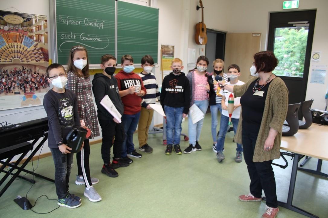 Mehrere Schülerinnen und Schüler und Lehrerin im Klassenraum bei der Produktion eines Hörspiels