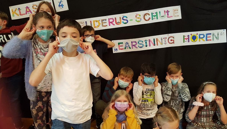 Mehrere Kinder massieren ihre Ohren