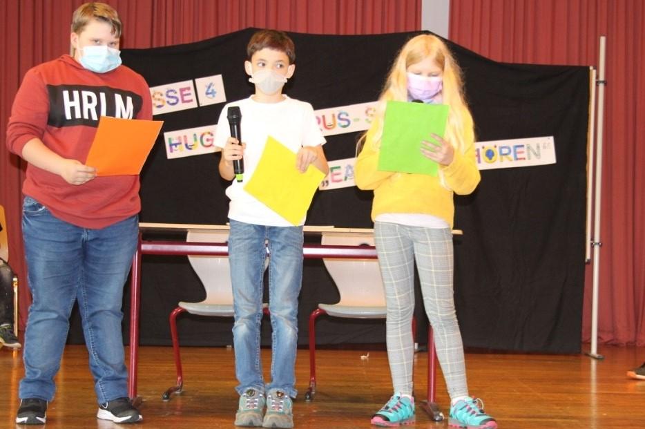 Drei Schüler auf einer Bühne mit Mikrofonen