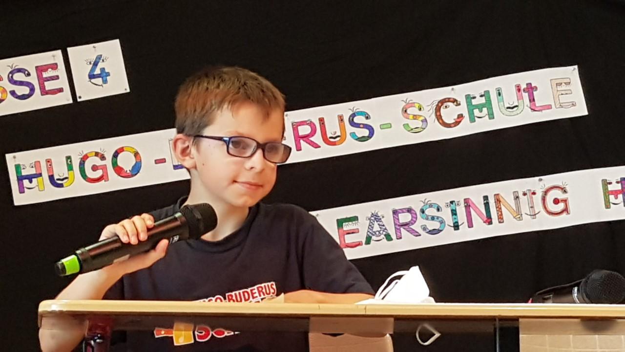 Junge spricht in ein Mikro