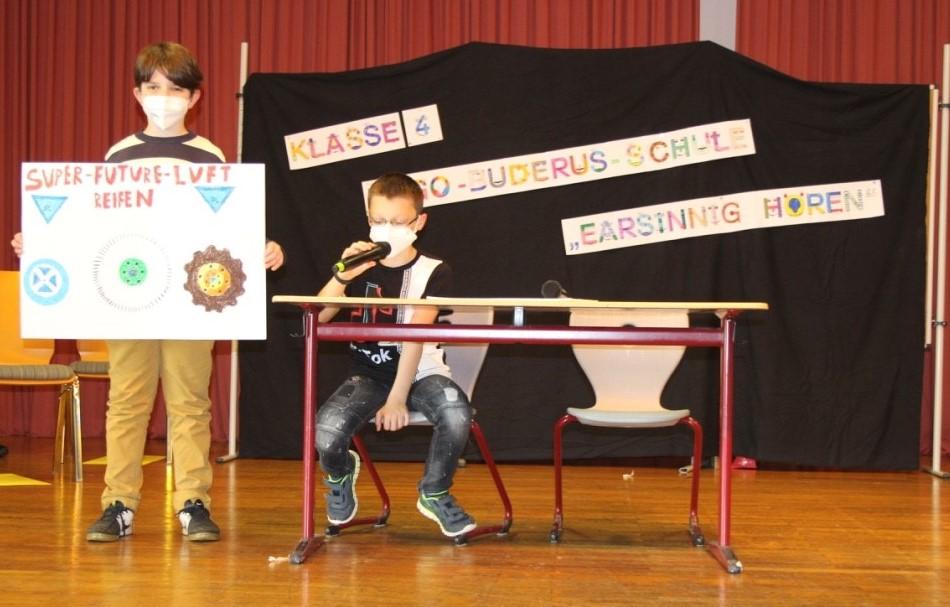 Zwei Jungen auf einer Bühne: ein Junge sitzt am Tisch und spricht in ein Mikro, ein anderer Junge hält ein Plakat mit gezeichneten Autoreifen