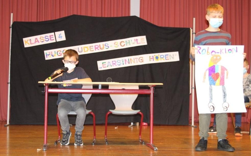 Zwei Jungen auf einer Bühne: ein Junge sitzt am Tisch und spricht in ein Mikro, ein zweiter Junge hält ein Plakat mit einem gezeichneten Roboter hoch