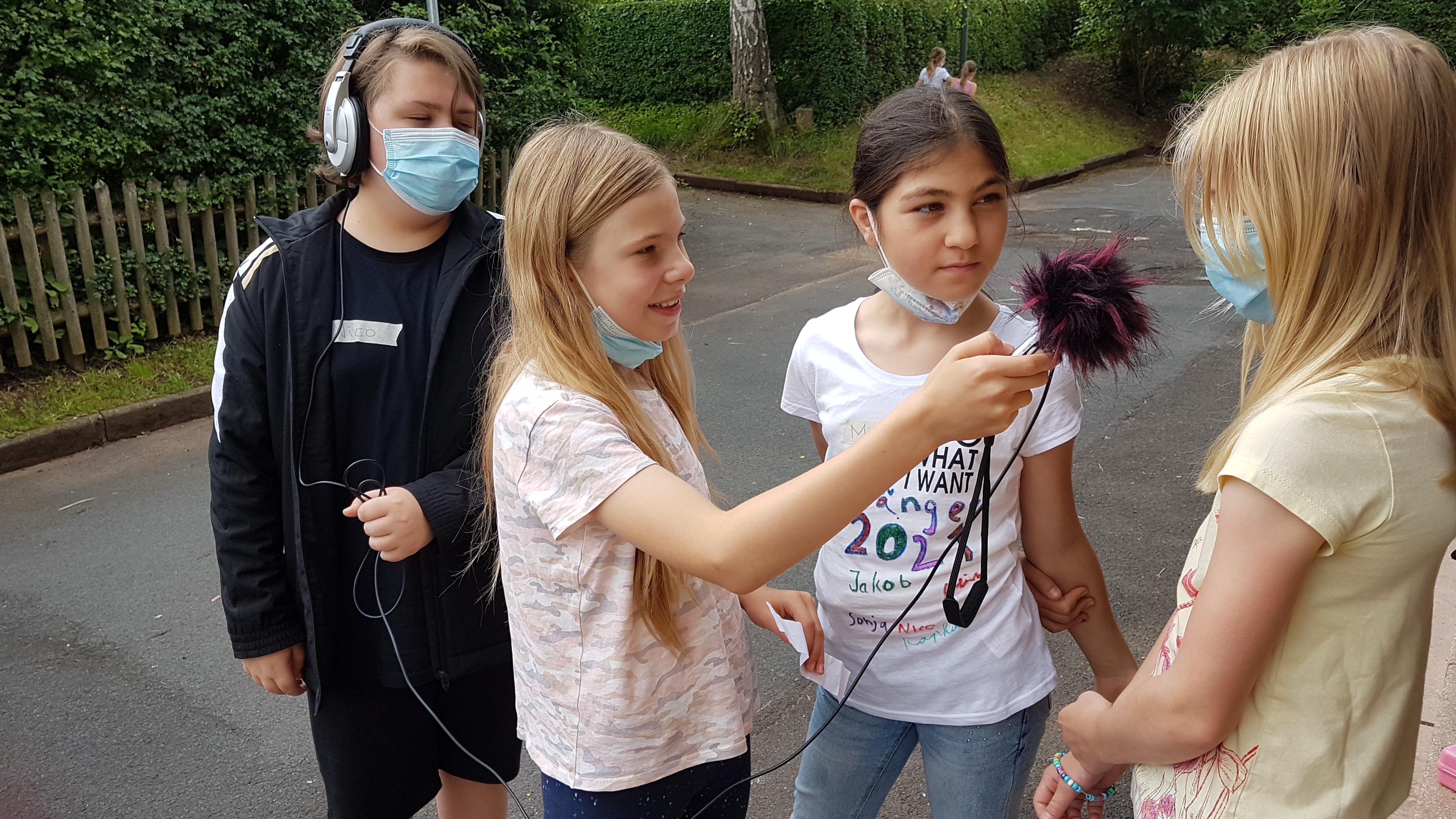 Kinder mit Mikrofon führen Interview