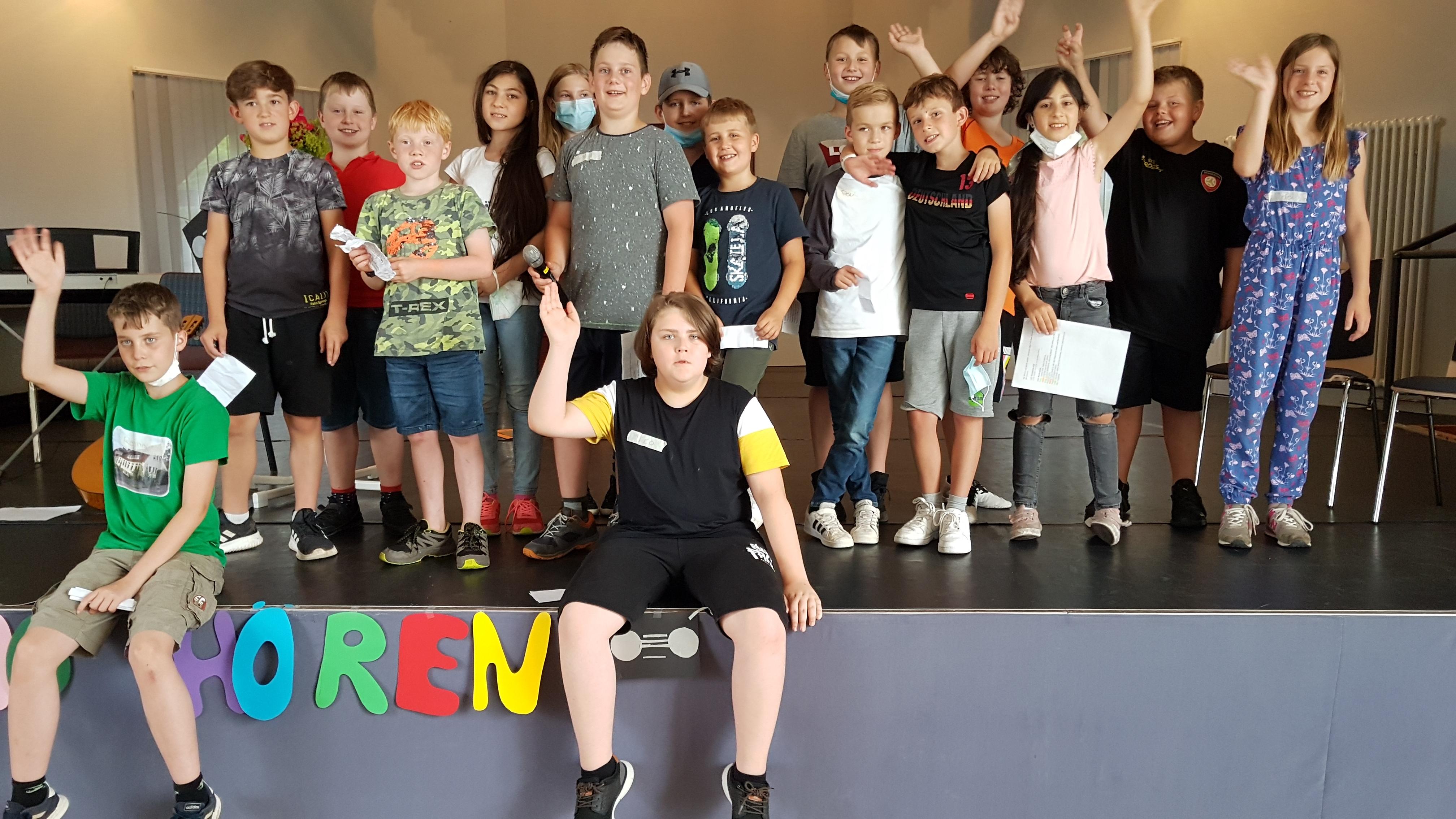 Gruppe von Kindern auf der Bühne winken in die Kamera