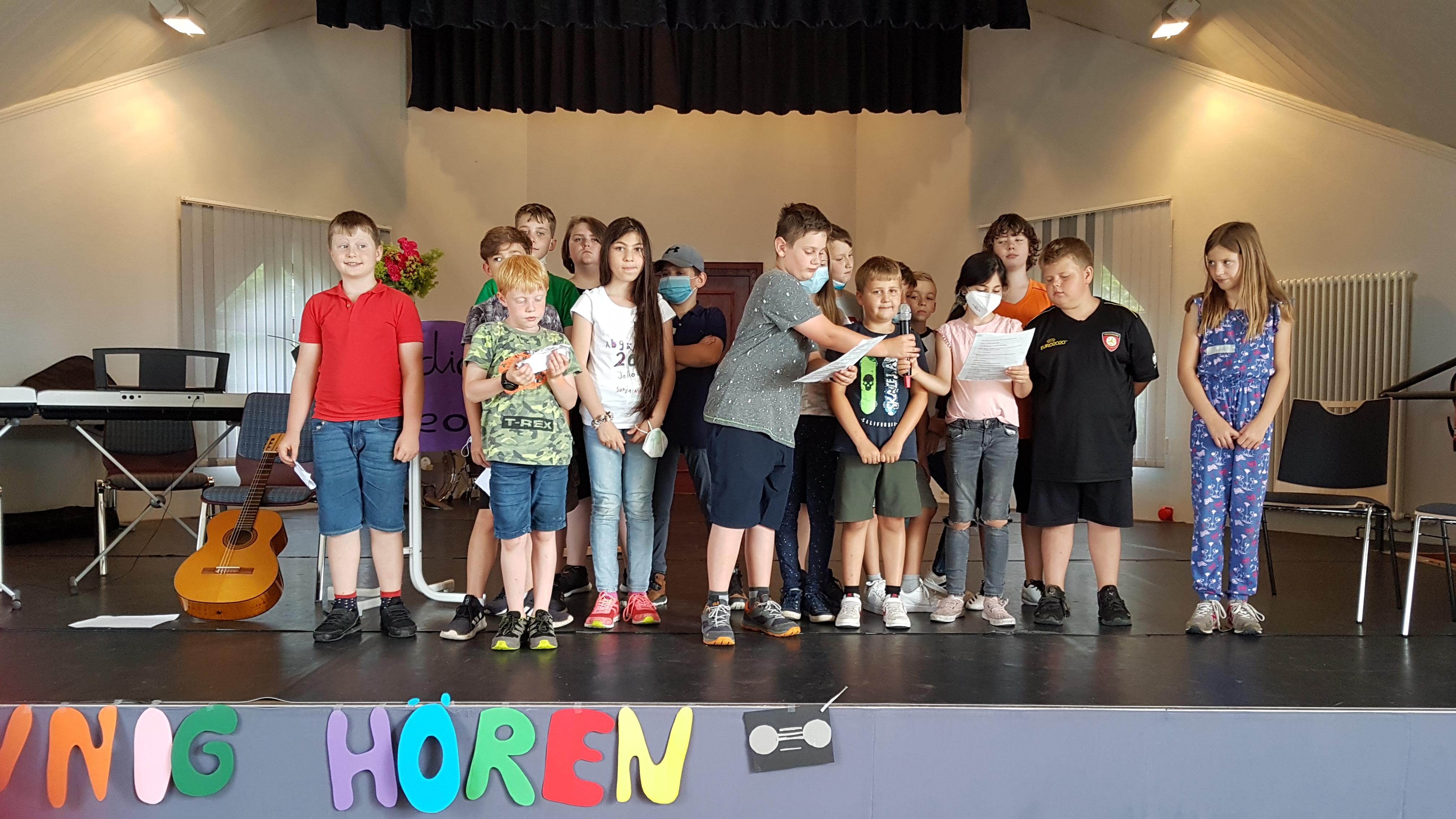 Gruppe von Kindern, die auf der Bühne vortragen