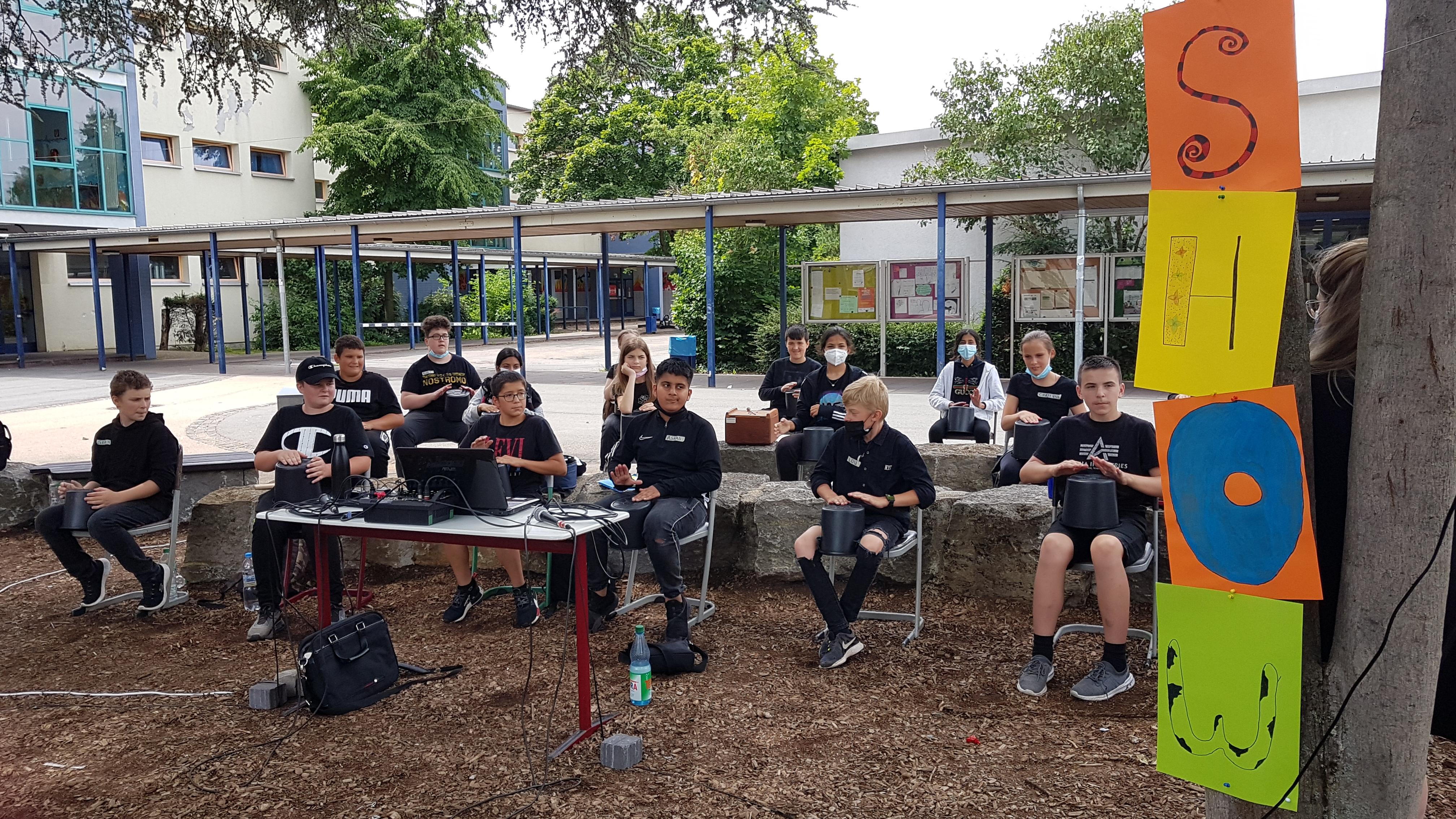 Gruppe von Jugendlichen sitzen auf Stühlen und trommeln mit den Händen auf Eimern
