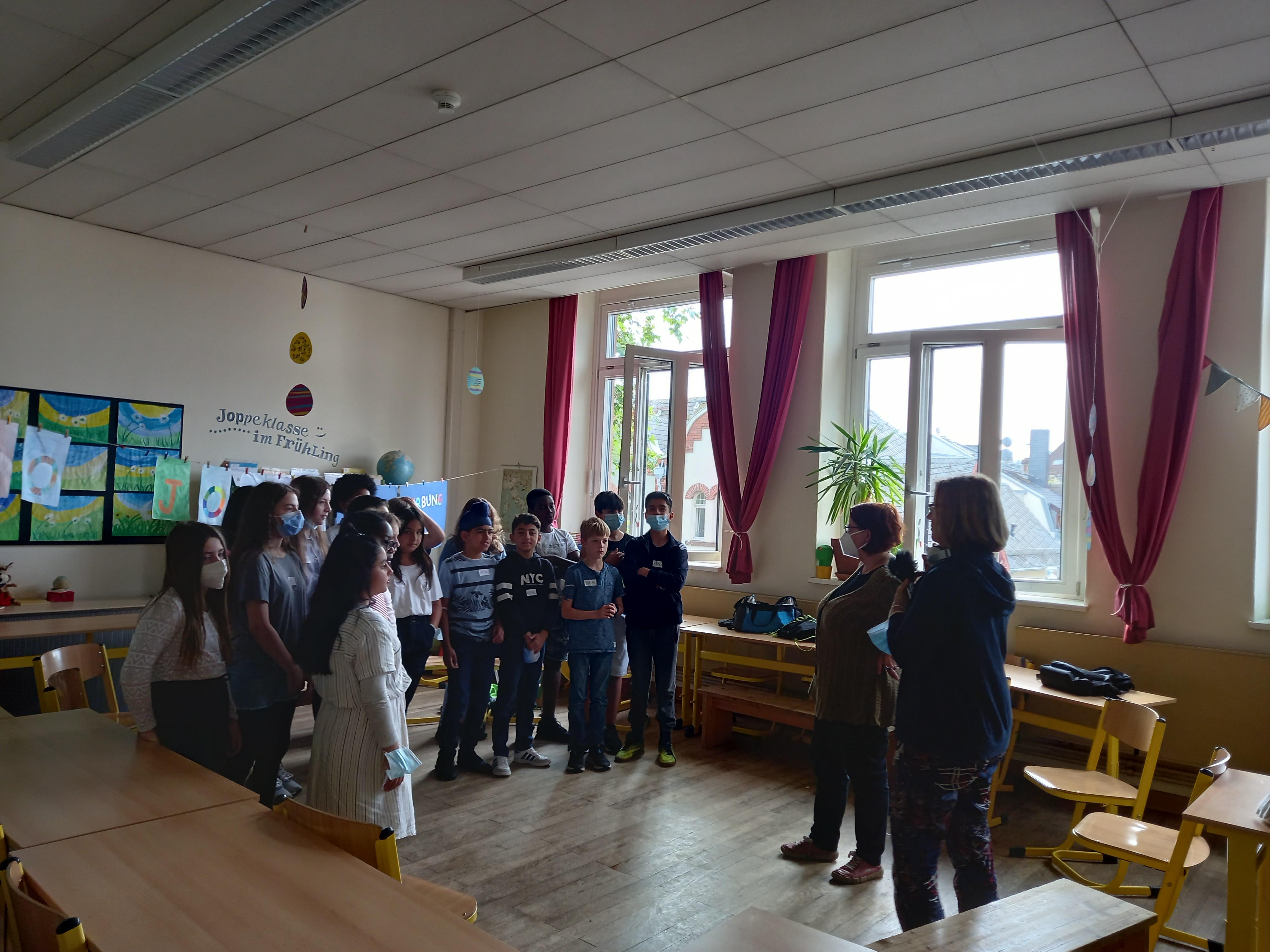 Gruppe von Schülerinnen, Schülern und Lehrerinnen im Klassenraum