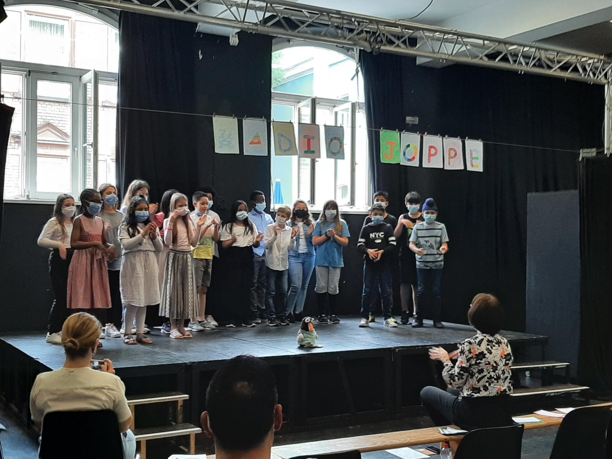 Gruppe von Schülerinnen und Schülern auf einer Bühne